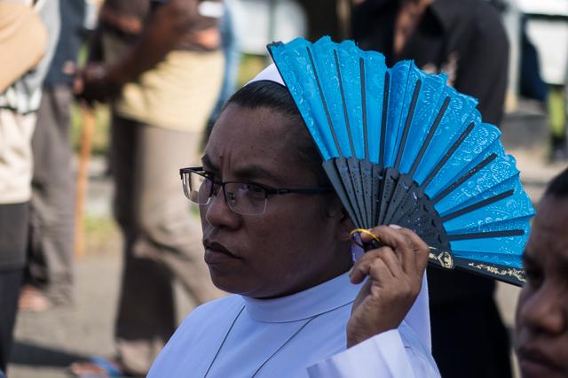 A nun shields her head from the sun